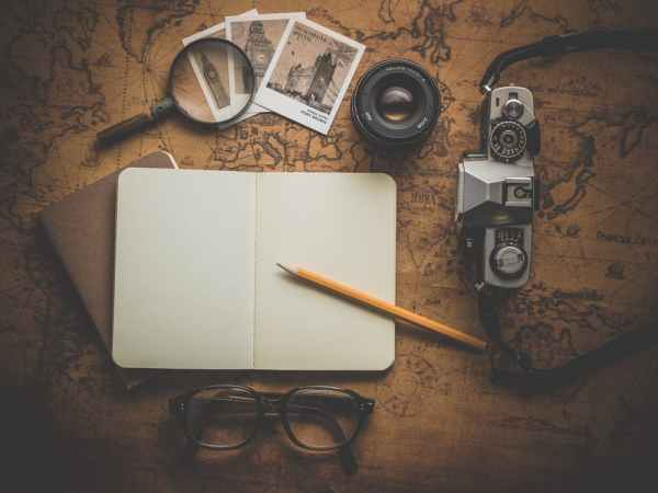 A pencil and notebook surrounded by photos and cameras.