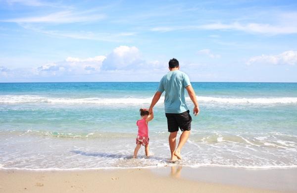 A man walking his daughter at the beach.